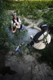 Deux insurgés Taliban plaisantent en faisant leurs ablutions avant de prier. Ils s'agenouillent face à la Mecque cinq fois par jour.