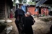 """COX BAZAR, BANGLADESH- SEPT, 2018: Yasmine agée de 4 mois s'est endormie dans les bras de sa mère Shafiqa (20). Yasmine a la peau claire et les traits un peu bridés. Elle est le fruit du viol de sa mère par les soldats birmans le 24 aôut 2017. Shafiqa a réussi à convaincre son mari de la garder et de faire comem si elle était sienne. Elle est tolérée dans la famille, mais le secret doit être gardé à tous prix pour que Yasmine ne soit pas stigmatisée et rejetée par la communauté Rohingya qui a des problèmes avec ces bébés de la honte qu'elle appelle """"fils de Birmans"""".  (Picture by veronique de Viguerie/Getty Reportage)"""