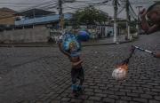 RIO, BRESIL-MARCH, 2019: Un membre du gang des Cobras apprend à son fils à manier la bâton et la balle que l'on frappe fort sur le sol pour faire peur. (Picture by Veronique de Viguerie/Getty Reportage)