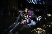 SITTWE, MYANMAR- JUNE, 2015: Bodouba camp.  A family is working in recycling fishnets. The baby is severely malnourished as many Rohingya babies. (Picture by Veronique de Viguerie/Reportage by getty Images).