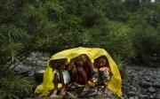 SURIGAO, MINDANAO- JUNE, 2017: Des petites filles Lumad regardent la cérémonie en s'abritant de la pluie. Craignant de se faire chasser par une exploitation minière, les Lumads qui sont animistes font une cérémonie au cours de laquelle ils sacrifient un cochon. Le prêtre implore les dieux d'éloigner les exploitations minières pour qu'ils puissent rester sur leur terres ancestrales et continuer de vivre avec la nature.  Little Lumad girls are watching the ceremony. Fearing to be kicked out by a mining exploitation, the Lumad who are animist are making a ceremony, scarificing a pig. The priest is begging the gods to keep away the mining exploitation so they can stay in their ancestral forest. (Picture by Veronique de Viguerie/Reportage by Getty Images)