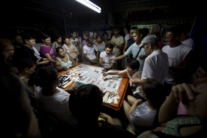 MANILA, PHILIPPINES - OCT, 2016: Neignbourgs are betting and playing cards in front of Flor John's house. The money made will help with the funeral services. Flor John (34), drug user, was executed by some apparent policemen at his house on the 19th of October. He was the father of three and married with Rita Cruz.  (Picture by Veronique de Viguerie/ Reportage by Getty Images).
