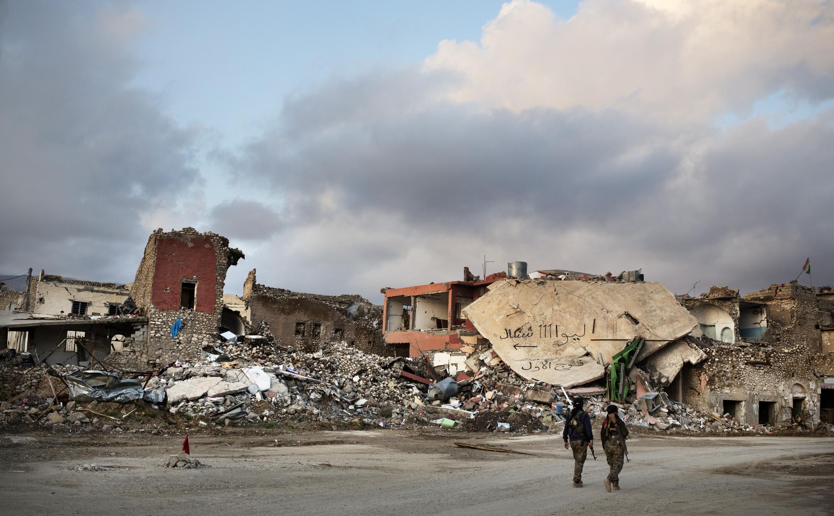 SINJAR, KURDISTAN, IRAQ- FEBRUARY, 2016: Shilan (casquette) Yezidie combattante du YBS marchent avec sa camarade dans les ruines de la ville martyr de Sinjar. Des obus et des mortiers de Daech continuent de tomber. (picture by Veronique de Viguerie/ Reportage by Getty Images )
