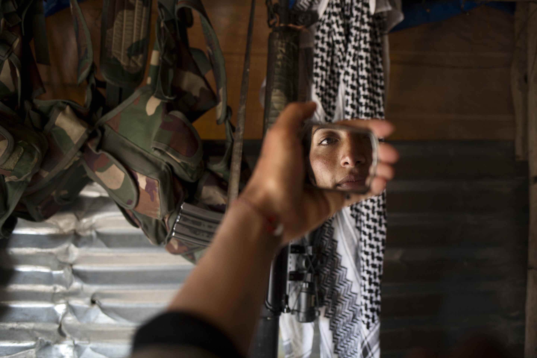 SINJAR, KURDISTAN, IRAQ- FEBRUARY, 2016: Norouz (21) se recoiffe devant un fusil d'assault pris à un membre de Daesh tué par ses camarades il y a quelques jours.(picture by Veronique de Viguerie/ Reportage by Getty Images )